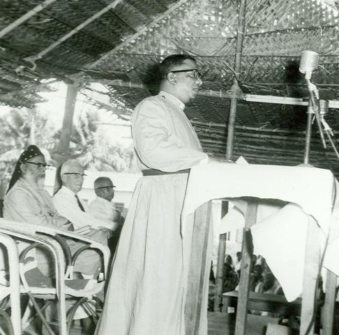 Bishop T. S. Joseph speaking at the Maramon Convention while Bishop Alexander Mar Theophilus (Metropolitan Alexander Mar Thoma), E. Stanley Jones and Mr. Ramenpillar listen.