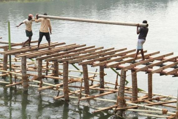 BALANCING ACT: Construction of a temporary footbridge linking the convention venue and the western bank of river Pampa progressing at Maramon near Kozhencherry. Photo: Leju Kamal